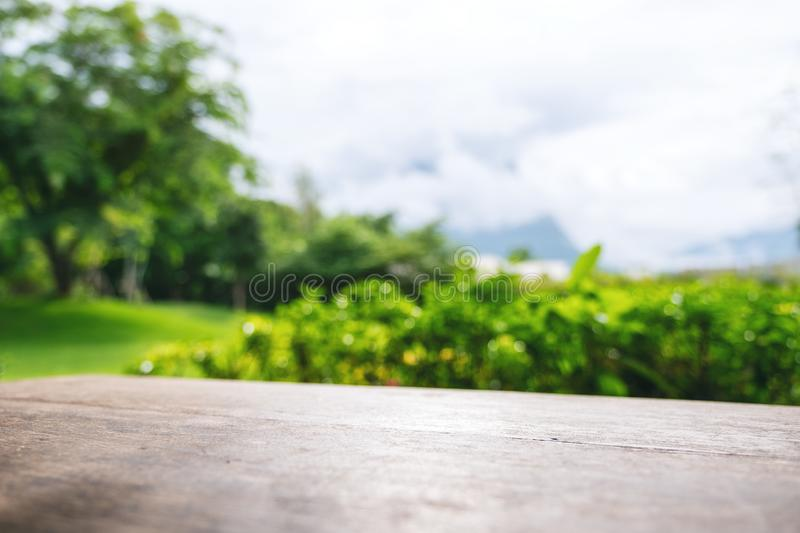 A vintage wooden table with blur green nature background. Closeup image of a vintage wooden table with blur green nature background royalty free stock photo