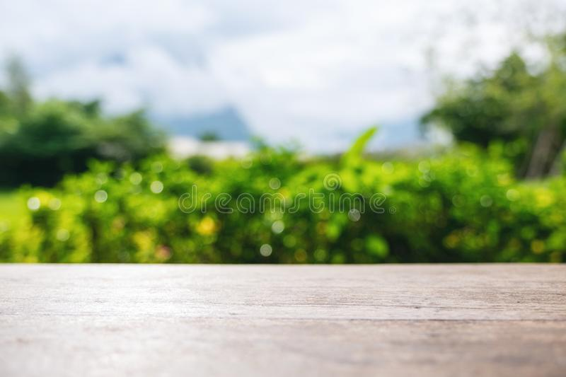 A vintage wooden table with blur green nature background. Closeup image of a vintage wooden table with blur green nature background royalty free stock image