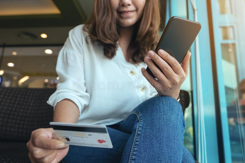 A woman holding credit card and using mobile banking while sitting in cafe. Closeup image of a woman holding credit card and using mobile banking while sitting royalty free stock photography