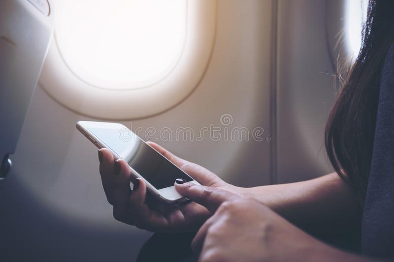 Closeup image of a woman holding and touching at white smart phone next to an airplane window with clouds and sky stock photo