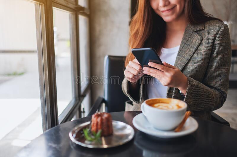 A woman holding and using mobile phone with coffee cup and snack on the table in cafe stock photos