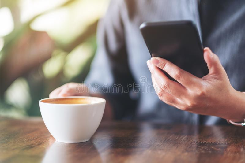 A woman holding  and using mobile phone while drinking coffee on wooden table in cafe royalty free stock image