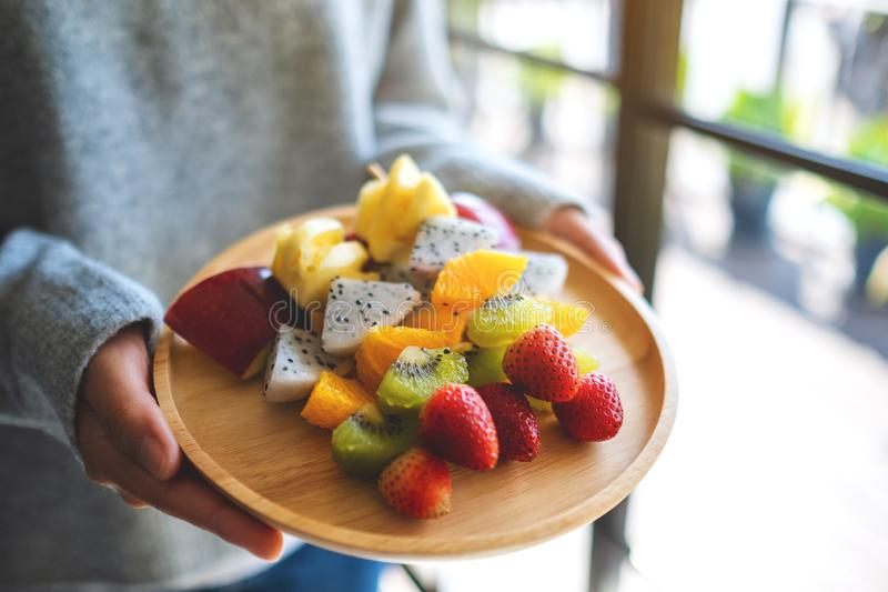 A woman holding a wooden plate of fresh mixed fruits on skewers royalty free stock images