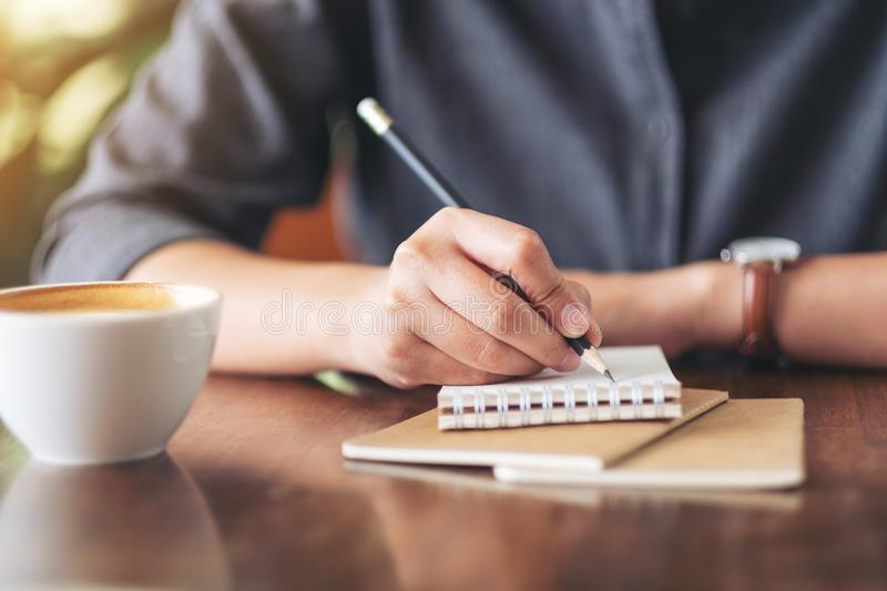 A woman`s hand writing on blank notebook with coffee cup on table in cafe stock photos