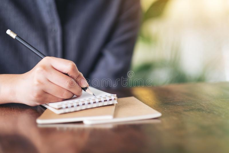 A woman`s hand writing on blank notebook on wooden table stock photo