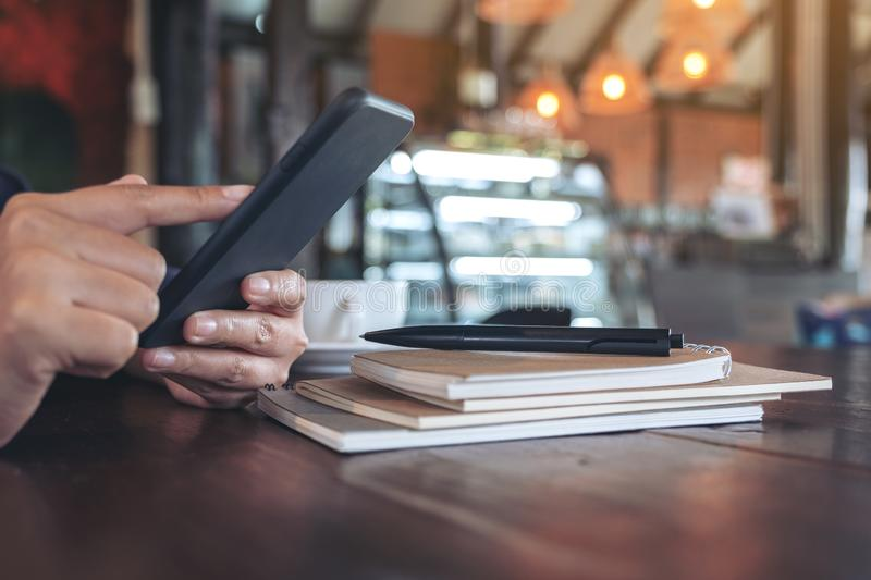 Woman`s hands holding and pointing at smart phone with notebook on wooden table in cafe. Closeup image of woman`s hands holding and pointing at smart phone with royalty free stock photo