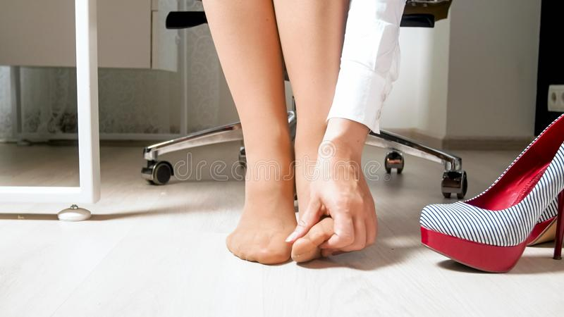 Closeup image of young busineswoman with varicose massaging her feet. Closeup photo of young busineswoman with varicose massaging her feet stock images