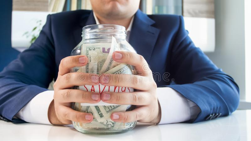 Closeup photo of young greedy businesman holding glass jar full of money in hands stock photos