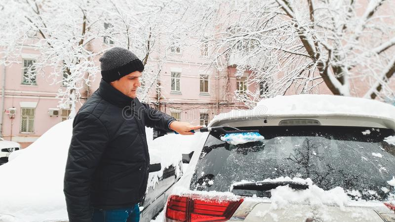 Closeup image of young handsome man in black coat and hat trying to clean up snow covered car after blizzard with black stock photography
