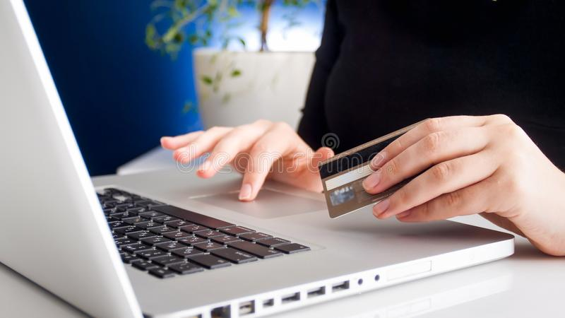 Closeup photo of young woman doing onkine shopping and holding credit card royalty free stock photography