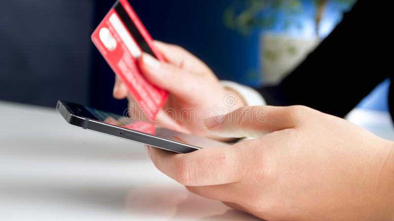 Closeup image of young woman making online purchases with credit card and smartphone stock photo