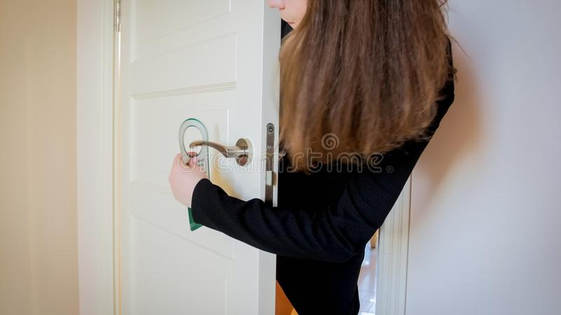 Closeup image of young woman putting do not disturb sign on door handle stock images