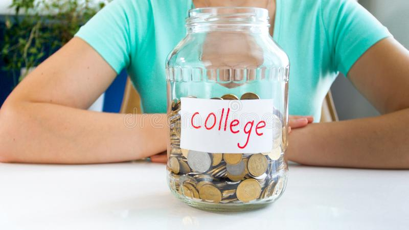 Closeup image of young woman saving money for education in college stock photography