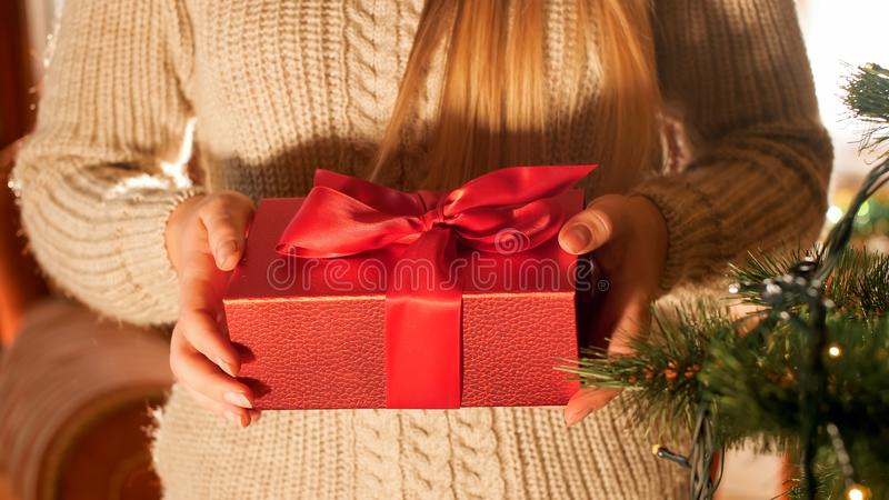 Closeup image of young woman in sweater holding Christmas gift box with red ribbon. Closeup photo of young woman in sweater holding Christmas gift box with red stock image