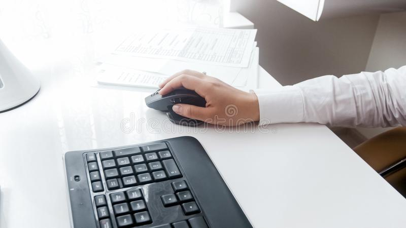 Closeup image of young woman using computer mouse at office stock photography