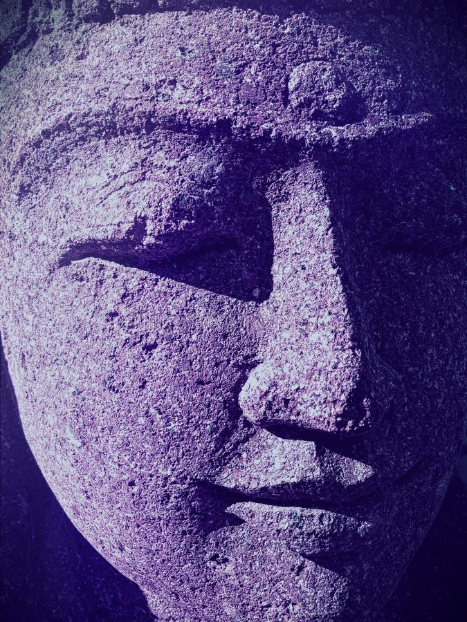 Closeup of Indian woman statue face with closed eyes and ultraviolet shadows stock photo