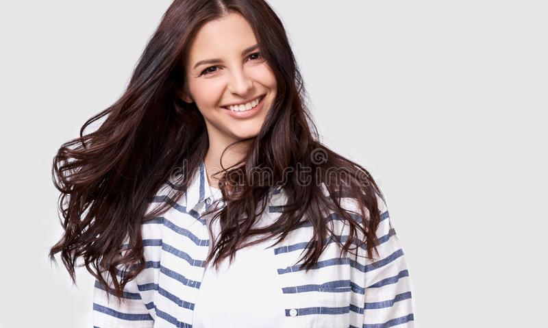 Closeup indoor portrait of beautiful brunette young woman with long hair smiling cheerfully. Charming female smile broadly showing royalty free stock photography