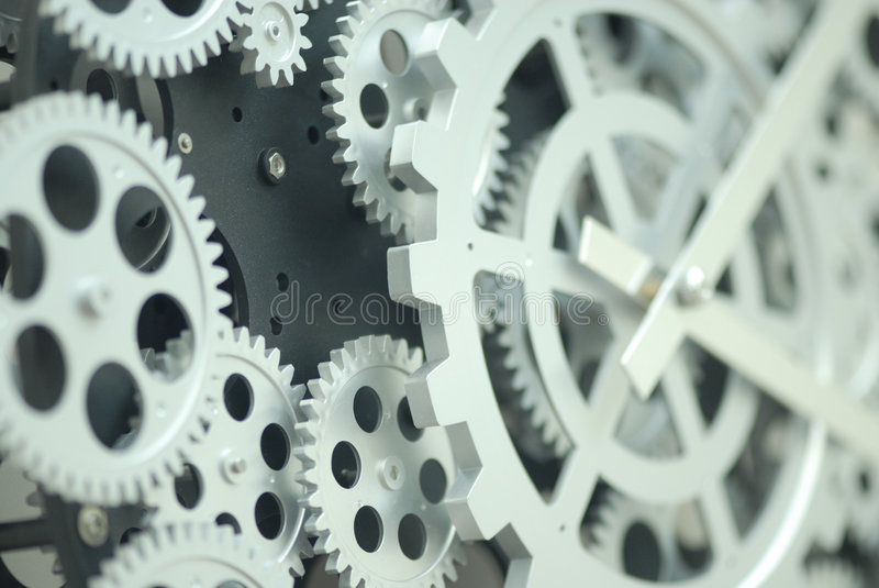 Closeup of inner clock gears. A closeup, detailed view of the gears and precision mechanisms inside of a mechanical clock stock image