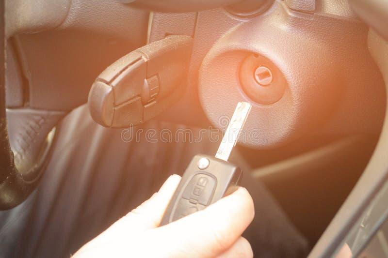 Closeup inside vehicle of hand holding key in ignition, start engine key stock image