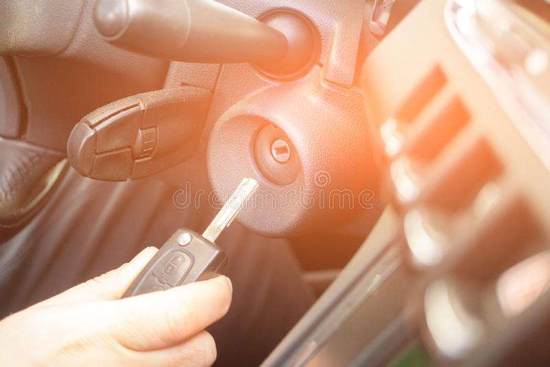 Closeup inside vehicle of hand holding key in ignition, start engine key royalty free stock photo