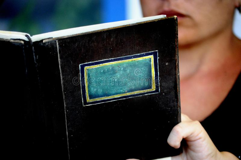 Closeup of an isolated book or manu with no title with a person reading behind on the background - space for writing royalty free stock images