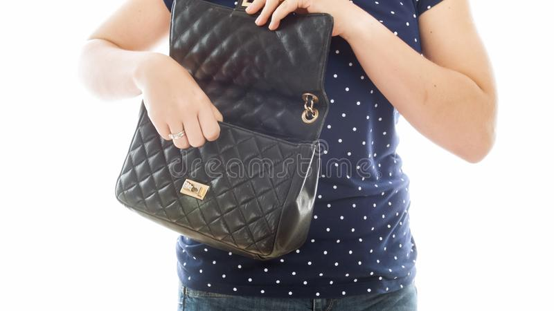 Closeup isolated image of young woman opens her black leather handbag stock image