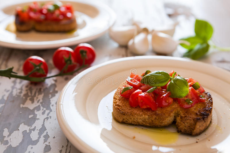 Closeup of Italian bruschetta with tomato and basil stock images