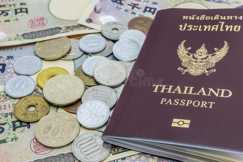 Closeup of Japanese Yen banknotes and Japanese Yen coin with Thailand passport. financial money and travel concept royalty free stock image