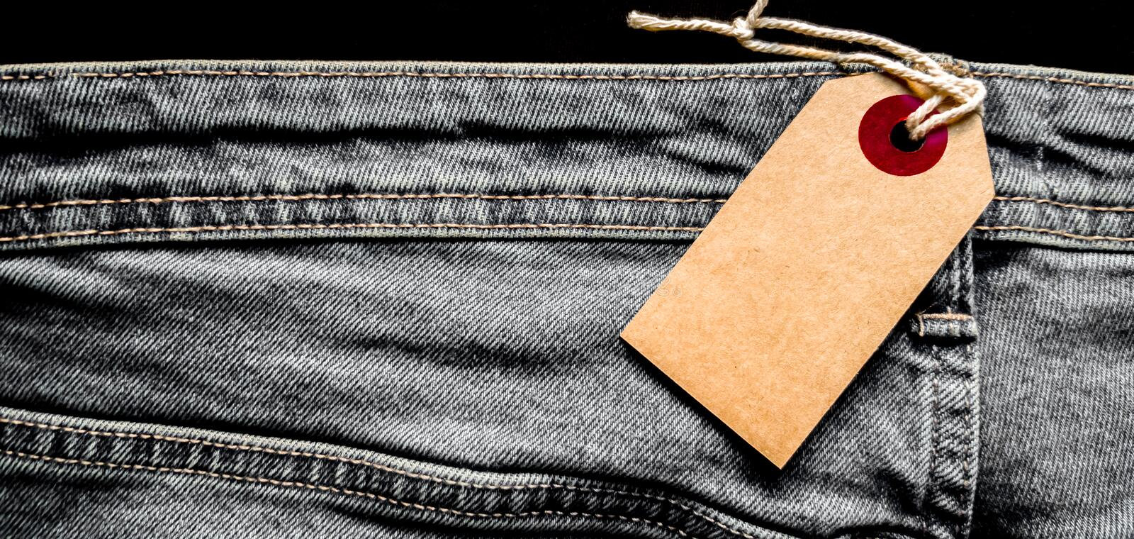 Closeup jeans with blank cardboard white price tag for your text. Tag the white mockup on the blue jeans. Empty copy space. stock photography