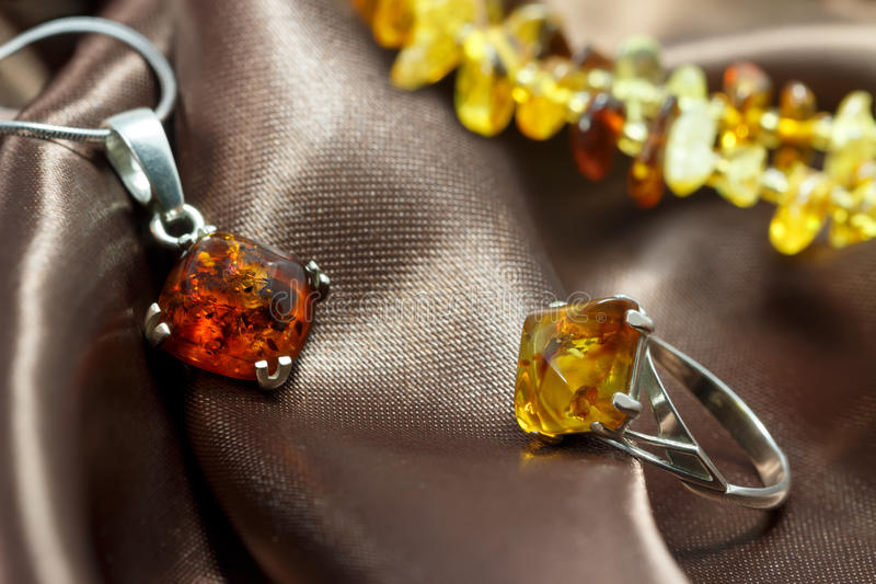 Closeup jewelry with authentic natural baltic amber : silver ring and pendant royalty free stock images