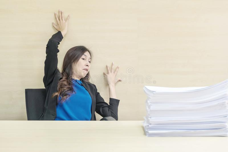 Closeup joke action of working woman are afraid pile of work paper in front of her in work concept on blurred wooden desk and stock images
