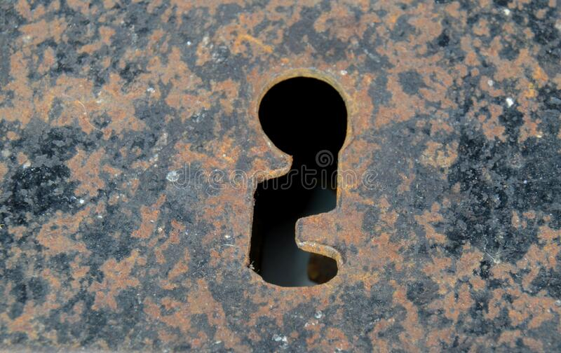 Closeup on the keyhole of an old rusty warded lock.  stock photo