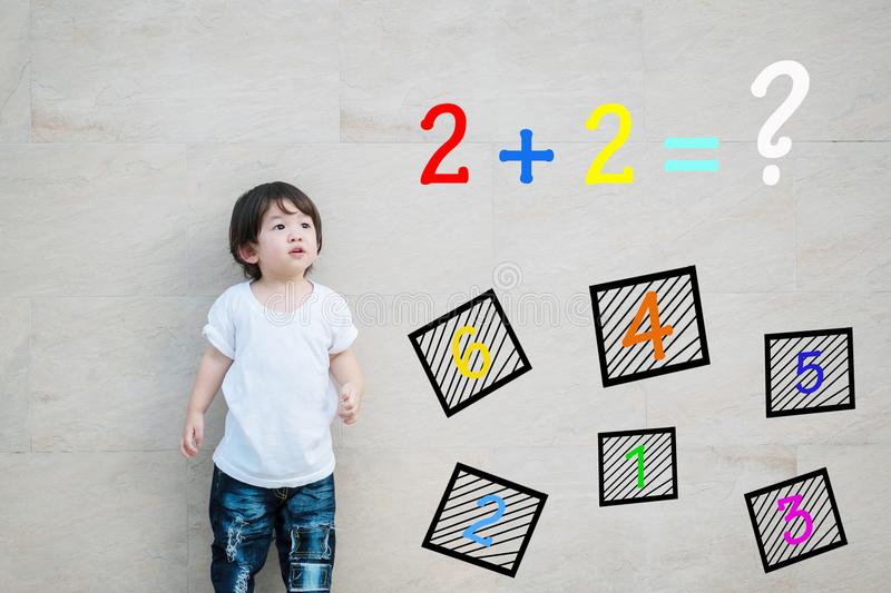 Closeup asian kid look at mathematic question on marble stone wall textured background. Closeup kid look at mathematic question on marble stone wall textured stock image