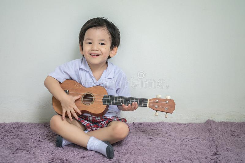 Closeup a little kid in student uniform play ukulele on carpet with copy space. Closeup a kid in student uniform play ukulele on carpet with copy space stock image