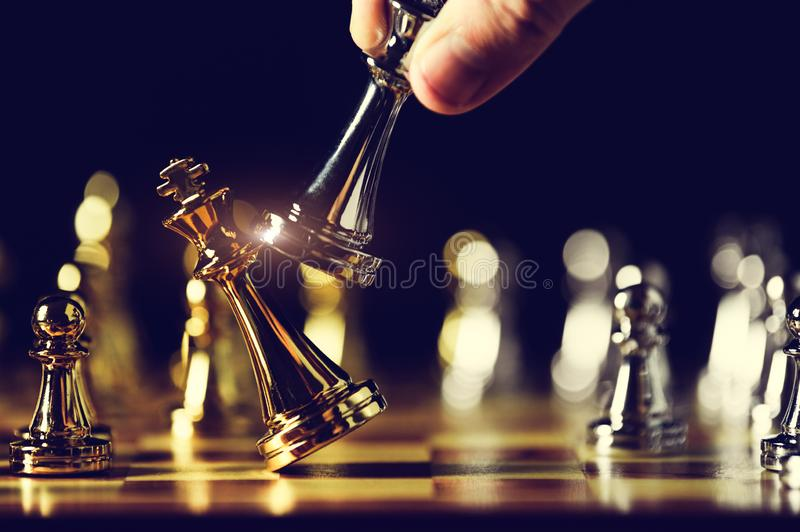 Closeup king chess piece defeated enemy or trade competitor by checkmate at end of chessboard game. Businessman moving chess to royalty free stock images