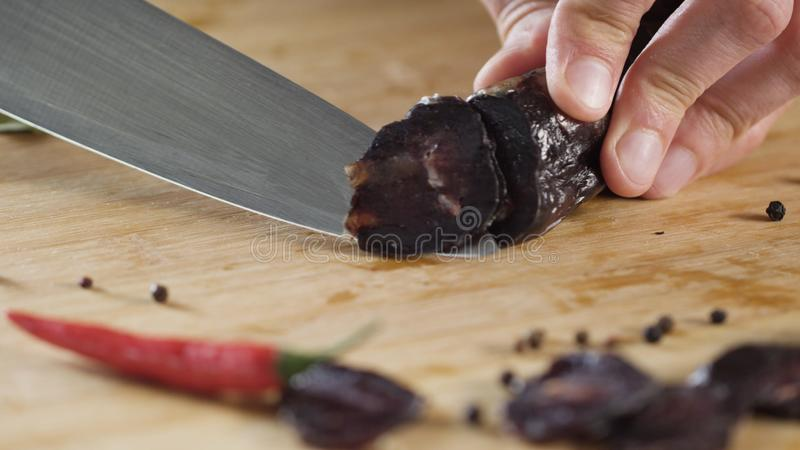 Closeup of knife cuts sausage. Scene. Close-up of cutting dark salami on wooden cutting board. Salt on background of royalty free stock photo
