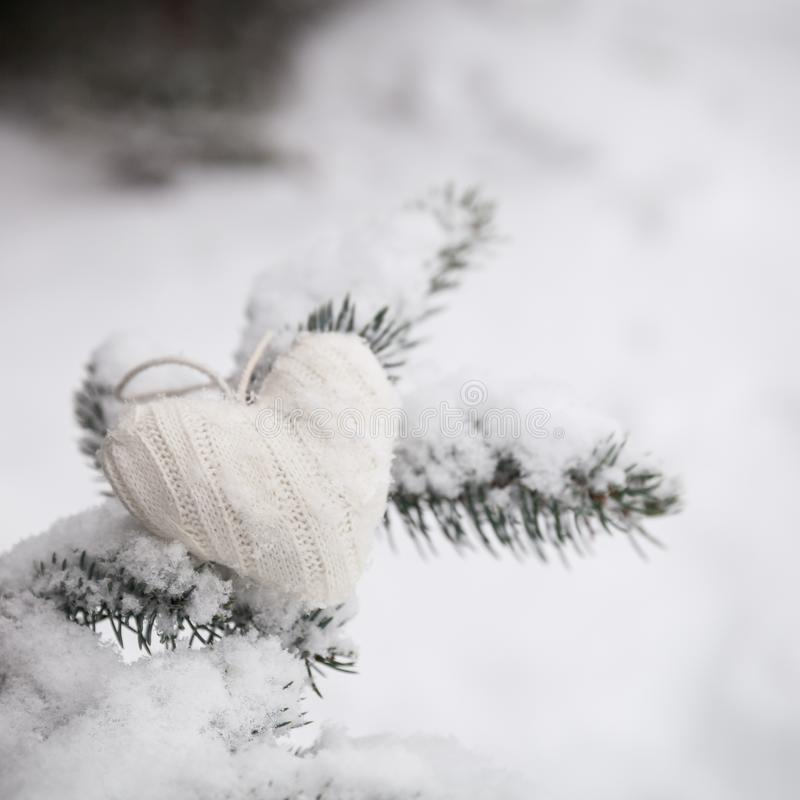Closeup of knitted heart Christmas decoration on Christmas tree with snow outdoors. Celebration, winter holidays concept stock image