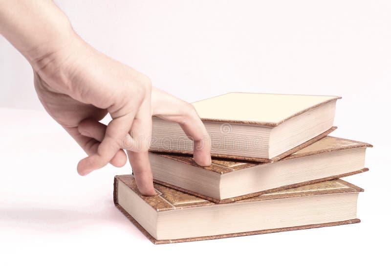 closeup la persona sta scegliendo un libro dalla pila Foto con lo spazio della copia fotografia stock