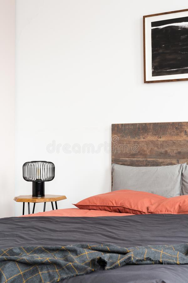 Closeup of lamp on wooden nightstand and black poster on the white wall of elegant bedroom interior with king size bed with wooden stock image