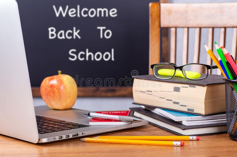 Closeup of Laptop Computer on School Desk. Closeup of laptop computer and stack of books on a desk with Back To School written on blackboard in background royalty free stock photography