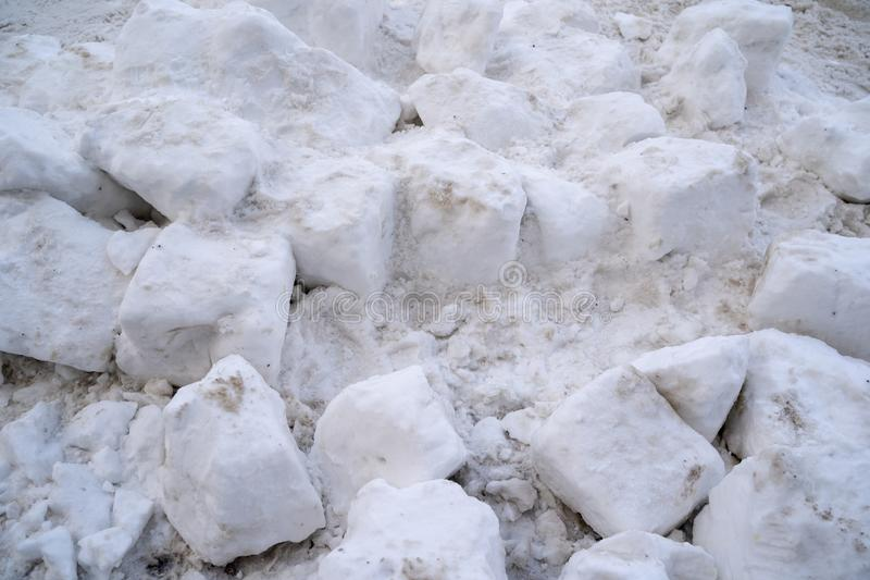 Closeup of large chunks of dirty snow, from a snowplow, on the street.  royalty free stock images
