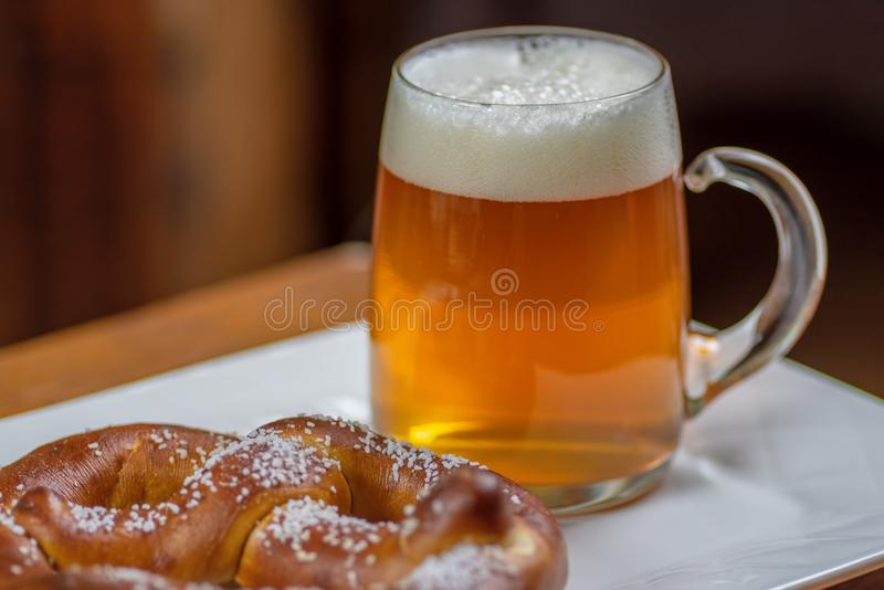Glass mug of beer and pretzel stock photography