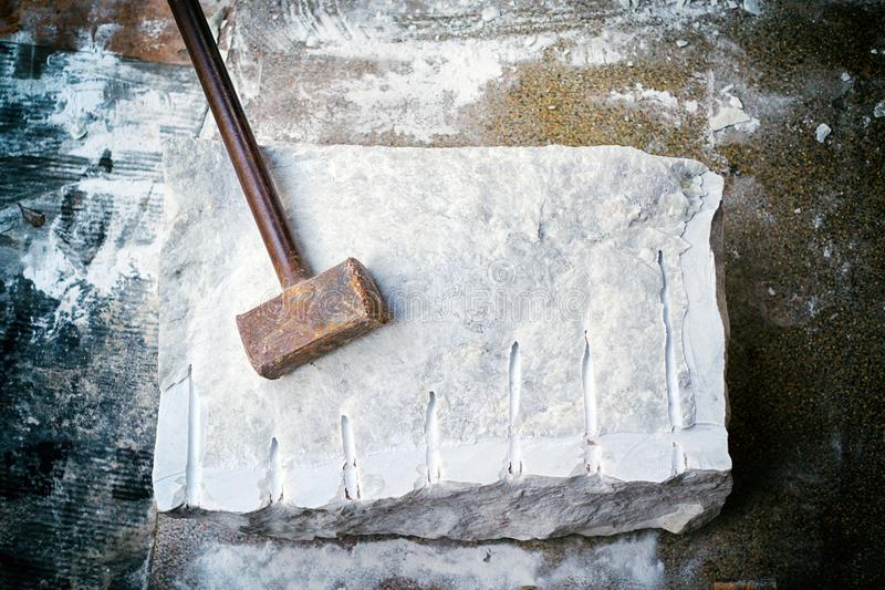 Closeup of a large piece of marble and a hammer after splitting. royalty free stock images