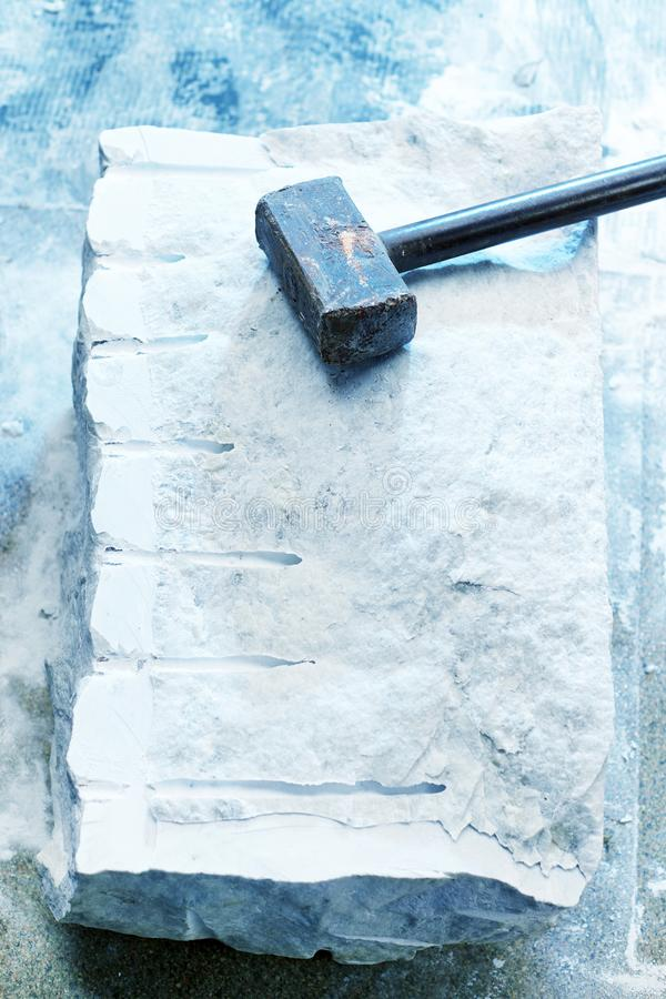 Closeup of a large piece of marble and a hammer after splitting stock photography