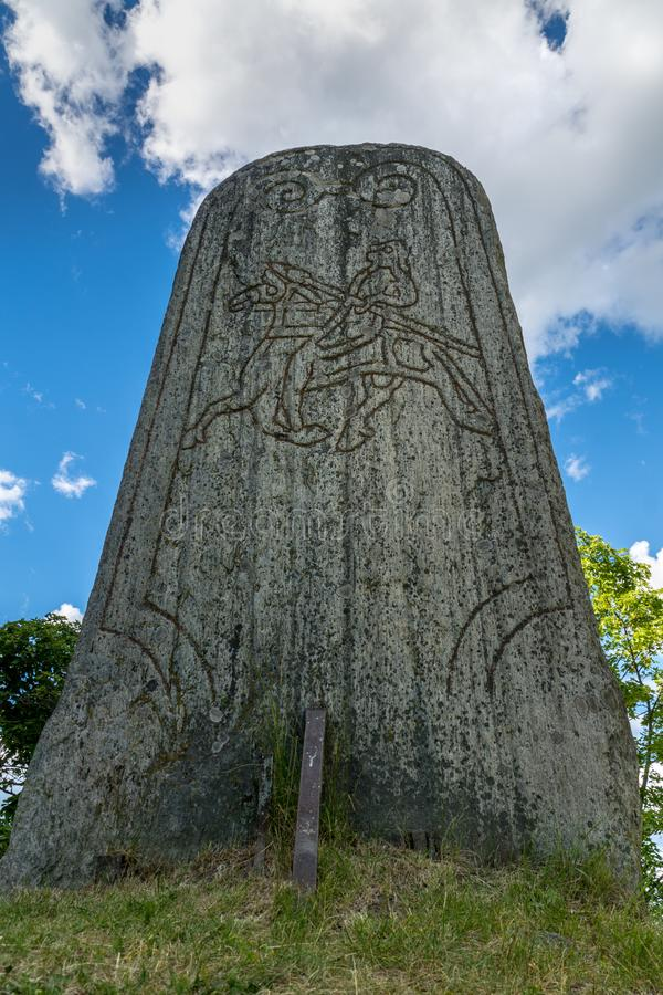 Closeup of a large rune stone from a low angle perspective. Large rune stone with a drawing of a man with a spear riding on a horse, taken from a low angle stock images