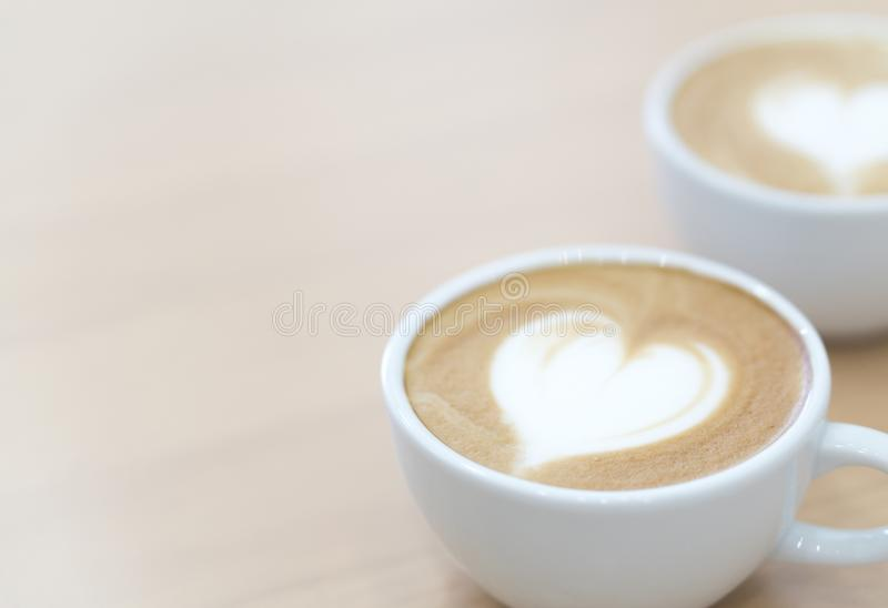 Closeup latte art coffee with heart shape in white cup for relax stock photos