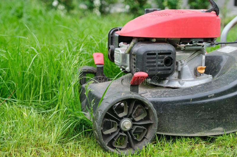 Closeup of lawn mower mowing green grass, city courtyard of an apartment building.  royalty free stock images