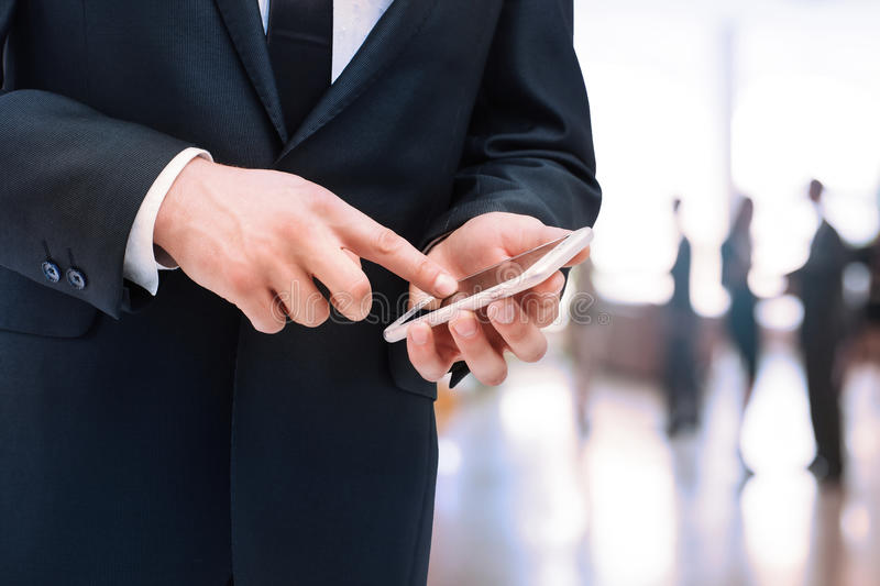 Closeup on the left side of the photo the hand of the businessman clicks on the cell phone screen on the background of stock photos