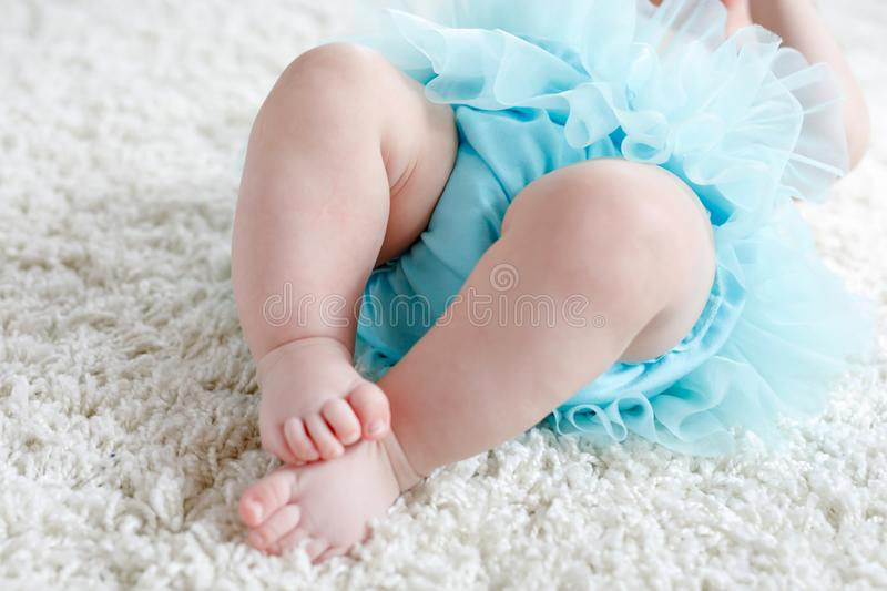 Closeup of legs and feet of baby girl on white background wearing turquoise tutu skirt. stock photos