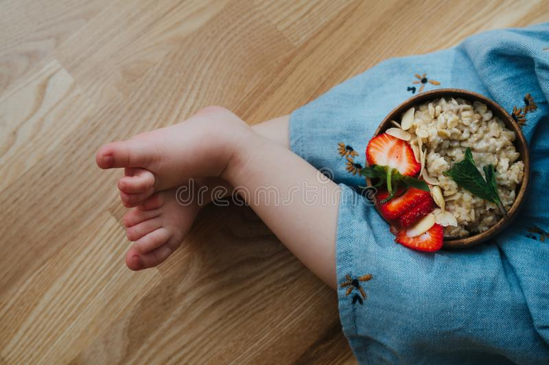 Closeup of legs little girl and a plate oatmeal with bananas and strawberries royalty free stock images